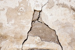 photographed close-up of a crack in the plaster walls of the old building.