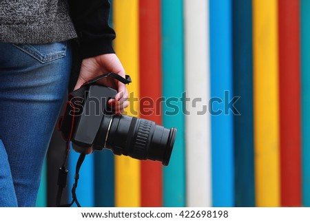 photographer holding  camera, close-up. Back view, Selective focus. colored vertical stripes in the background. #422698198