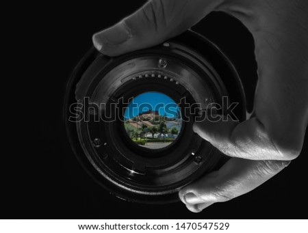 Photographer holds photographic lens, the focus is on the lens that reflects a beautiful medieval castle, with a black background