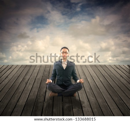 photos of business man relaxation on outdoor wood plank platform , lotus yoga stance