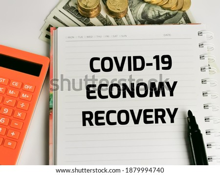 Phrase COVID-19 ECONOMIC RECOVERY on note book with dollar bank notes,marker pen,coins and a calculator.Covid-19 and business concept.  Stock photo ©
