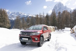 Pickup truck on road, Beautiful winter road under snow mountains Dolomites, Italy. Shiny red truck measuring the depth of the snow