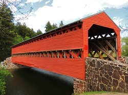 Picturesque wooden, red sachs covered bridge over marsh creek in spring in  gettysburg, pennsylvania