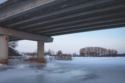 pillars under the bridge in winter on the ice of the river. big transport bridge in Latvia from under, winter evening light, clear sky, dry yellow reeds, snow covered ground