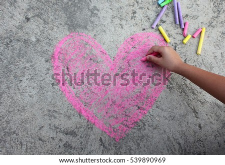 pink heart symbol is drawn on a sidewalk outside with chalk #539890969