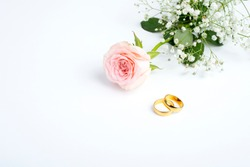 pink rose and wedding rings over white background