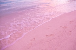 Pink sand beach on tropical Island, Bahamas. Bahamas Pink sand beach. Amazing tropical beach in Caribbean with pink sand clear ocean water. Wave and footprints at sunset time.Footprints on beach sand