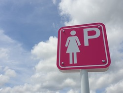 pink sign has a female symbol and the letter P to indicate that it is a female-only parking lot. With sky background