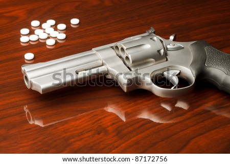 .357 pistol on wooden surface in front of pills drugs