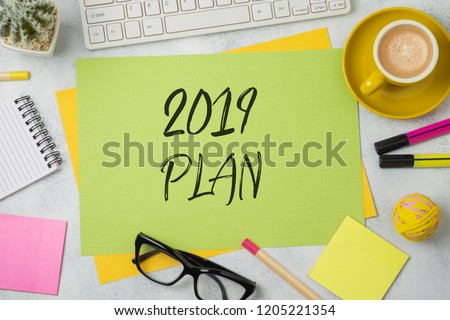 2019 plan text on colorful paper memo note with business office accessories. Top view from above