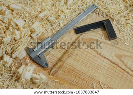 plane, a saw, a square, a pencil and other woodworking tools on an old workbench