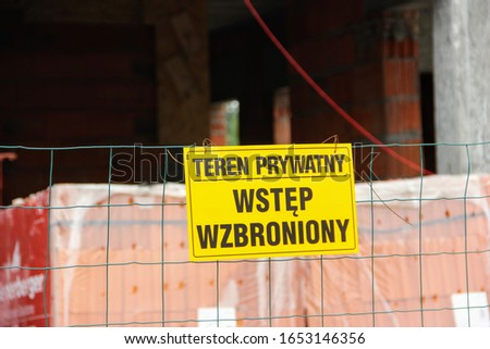 """Plaque placed on a fence made of mesh informing about the ban on entering the construction site in Polish """"Private area, no access""""."""