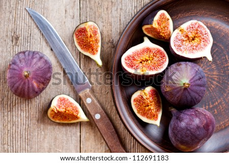 plate with fresh figs and old knife on rustic wooden table