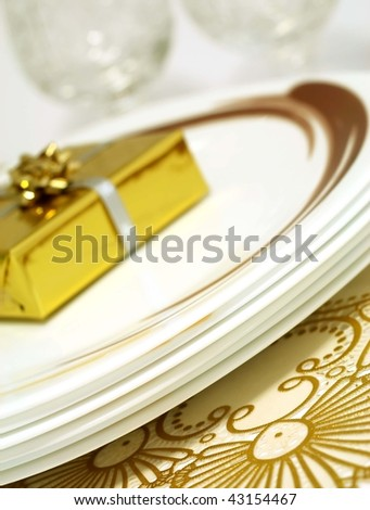 plates with gift on beautiful tablecloth