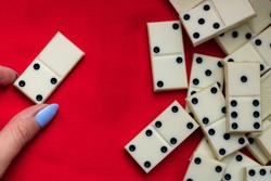 Play dominoes. A female hand lays domino bones on a red cloth next to a bunch of dominoes.