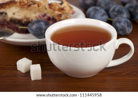 plums, fresh, cake and white cup on wooden background