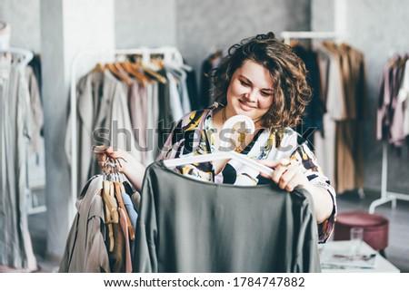 Plus Size Woman Choose Fashioned Dress in Store. Plus size women shopping. Foto stock ©