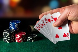 Poker cards with straight flush combination in the game. Close-up of a gambler hand is holding playing cards in poker club. Chips on green table