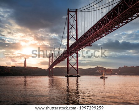 Ponte 25 de Abril Bridge in Lisbon during Sunset with ship and jesus monument, cloudy sky portugal Foto stock ©