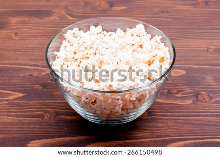Popcorn in a large bowl, standing in the middle of the table, side view