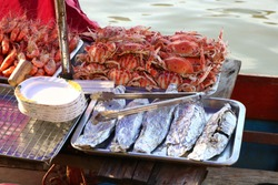 Popular seafood is sold on the boat at Amphawa Floating Market, Samut Songkhram Province, Thailand.
