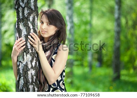 .Portrait of a beautiful young woman embracing a birch tree, European, White, Caucasian
