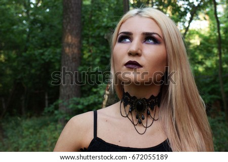 stock photo portrait of a blonde in the woods a witch black lips and a dark necklace around his neck 672055189