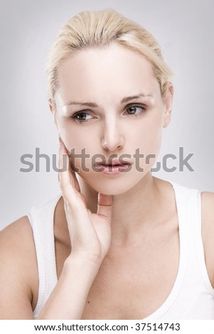 portrait of a caucasian blonde woman with toothache on grey background