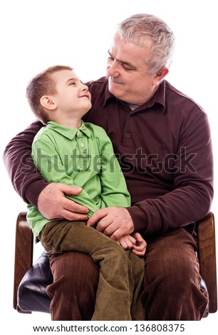 Portrait of a grandfather with his happy grandson sitting in armchair isolated on white background