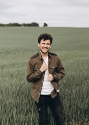 Portrait of a guy. the guy looks at the camera and smiles beautifully v touching his shirt.Outdoors lifestyle fashion close up portrait of pretty handsome guy, smiling and having fun.
