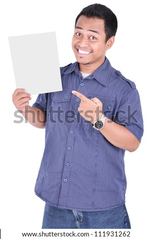 Portrait of a happy man holding a blank paper and pointing, isolated on white background