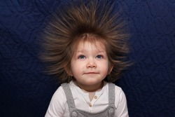 Portrait of a little smiling girl with electrified hair on a blue background. Electricity power concept.