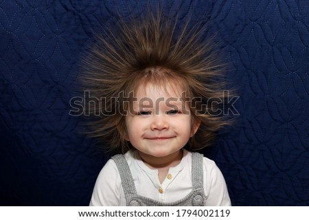 Photo of   Portrait of a little smiling girl with electrified hair on a blue background. Electricity power concept.