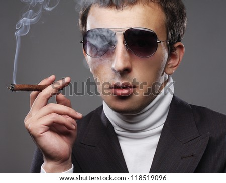 portrait of a man wearing sunglasses and smoking a cigerette.