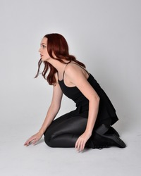 portrait of a pretty girl with red hair wearing black leather pants and top. Full length sitting pose isolated against a  grey studio background