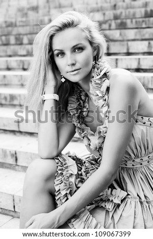 Portrait of a Young beautiful woman sitting on the ladder of old european city. Outdoors - stock photo