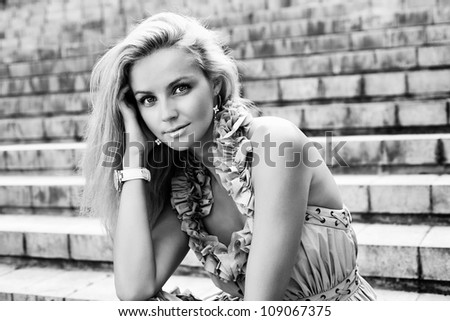 Portrait of a Young caucasian woman sitting on the ladder of old european city. Outdoors
