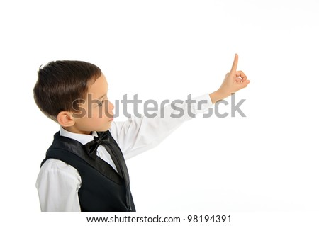 Portrait of a young school boy in black suit touching something with his finger isolated on white