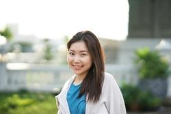 ฺportrait of beautiful Asian working woman enjoy free time in the park with blur and lens flare background