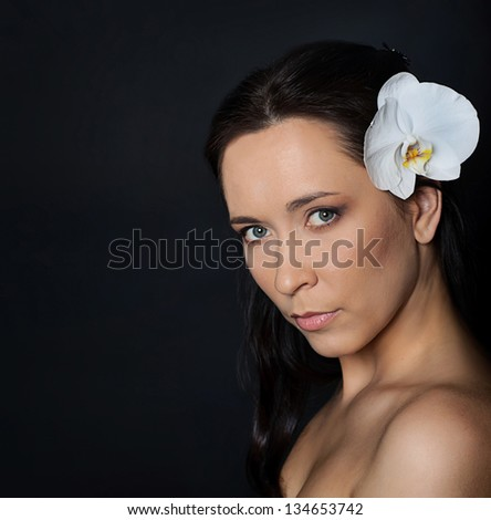 portrait of brunette woman with white orchid in hair over black