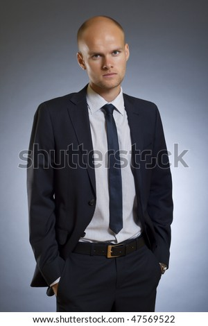 Portrait of businessman standing with hands in pocket in front of dark background