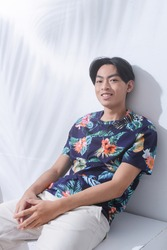 Portrait of handsome man w casual Summer wearing new stylish floral ,palm pattern T-shirts with white pants sitting chair palm shadow
