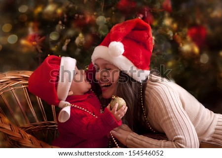 Portrait of happy mother and litlle baby in santa's hats