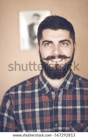 portrait of natural dark hair Caucasian man on orange background. Bearded hipster with clean shaved temples and stylish well-trimmed mustaches,happy and smiling #567292813