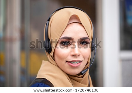 Portrait of Smiling friendly beautiful young muslim lady wearing hijab with headset working on support hotline in the office