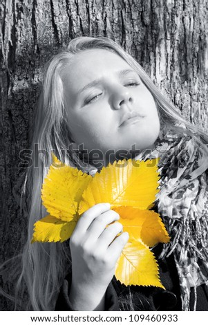 Portrait of the beautiful girl in black and white tone with yellow fall leaves