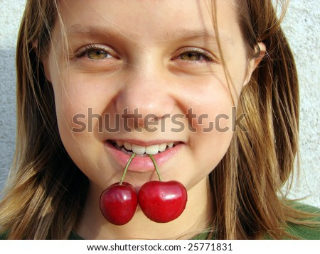 portrait of the beautiful girl with a sweet cherry in a teeth