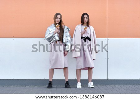 portrait of two  sister girls, eating ice cream cone, sure poker faces, grimaces,  no emotions, casual style, bright colors, orange white wall.  hipster girl #1386146087