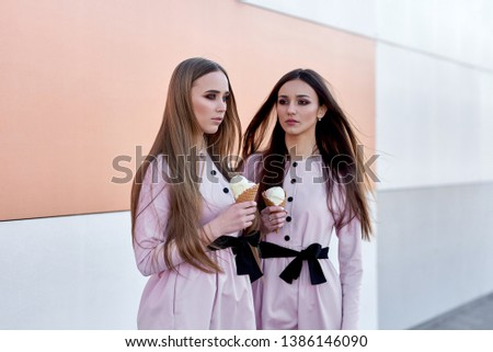 portrait of two  sister girls, eating ice cream cone, sure poker faces, grimaces,  no emotions, casual style, bright colors, orange white wall.  hipster girl #1386146090