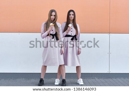 portrait of two  sister girls, eating ice cream cone, sure poker faces, grimaces,  no emotions, casual style, bright colors, orange white wall.  hipster girl #1386146093
